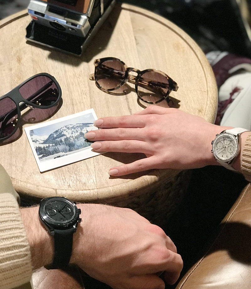View of 2 wrists wearing an Omega watch. Sunglasses on the table