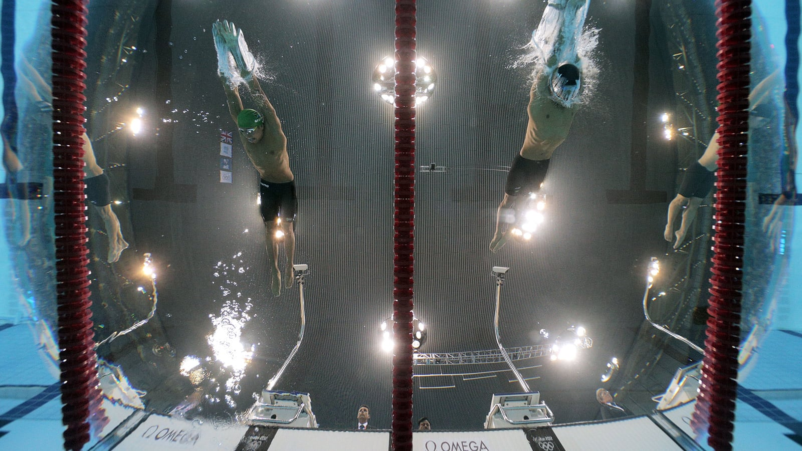 2 swimmers seen from the very bottom of the swimming pool