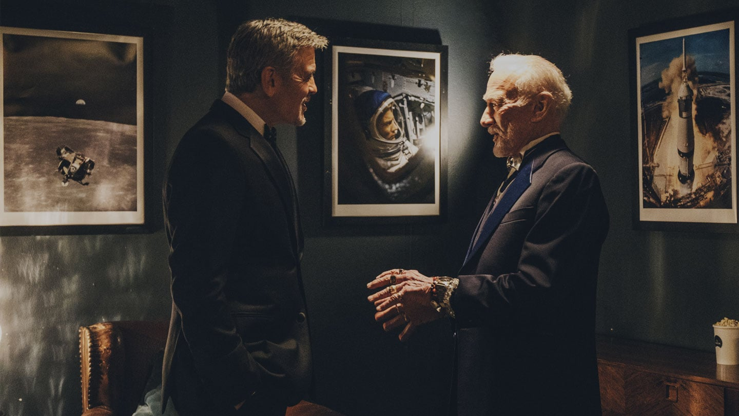 George Clooney talks with Buzz Aldrin in front of space pictures