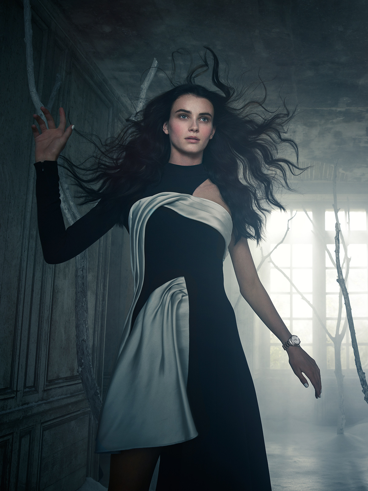 Picture of a woman with long dark hair walking in a corridor with dead branches coming from the floor