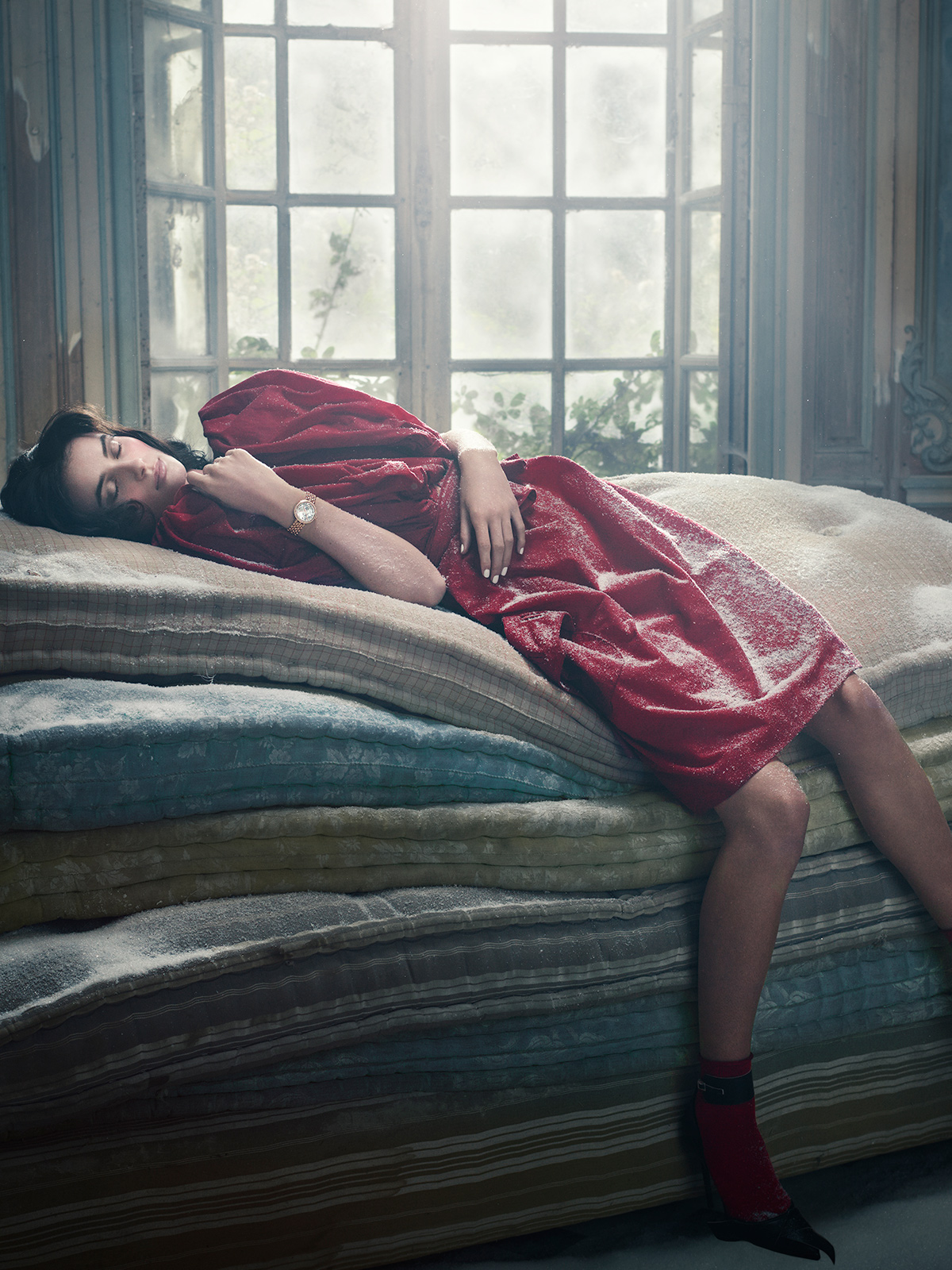 Dark haired woman in red dress sleeping elegantly on a pile of dusty mattress