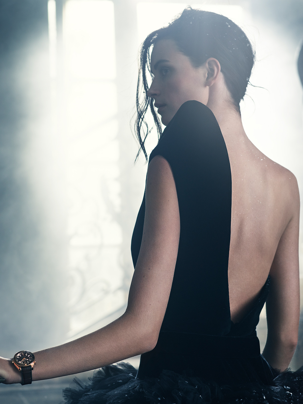 Half-length picture of a dark haired woman viewed from the rear wearing a black dress on only one shoulder