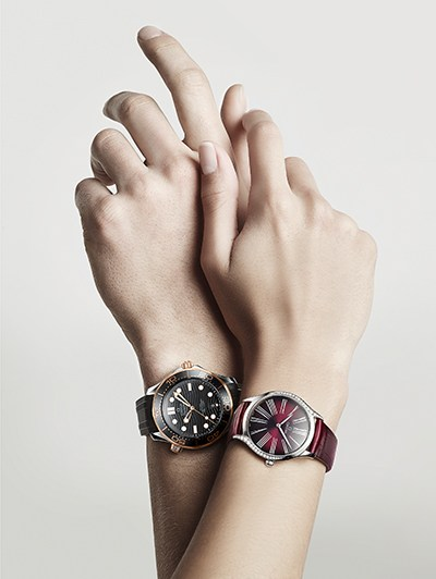 2 embracing hands wearing each an Omega watch