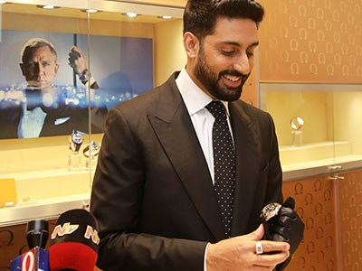 Abhishek Bachchan looking at the Omega watch he holds in his hand